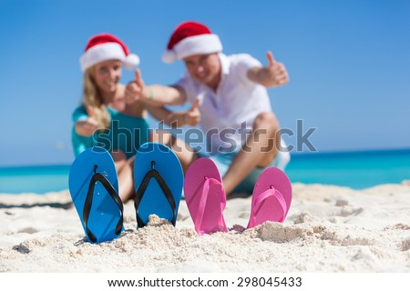 Caribbean Christmas vacation. Two pair of flip flops standing in a sand on background with  happy couple in Santa  hats, sitting on beach, smiling and showing thumbs up. Focus on sandals - stock photo
