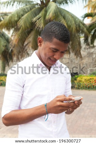 Caribbean guy writing a text message - stock photo