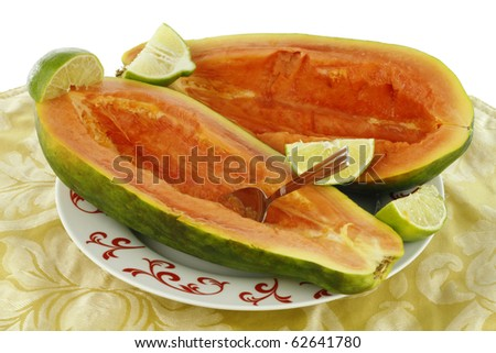 Caribbean red large fruit is freshly prepared and ready to eat with quartered lime. - stock photo