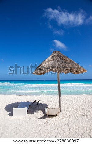 Caribbean sea coastline with grass sun umbrella and wooden beach beds. Vacation concept  - stock photo