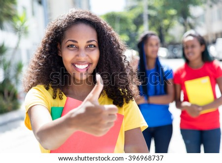 Caribbean student showing thumb in the city with friends - stock photo