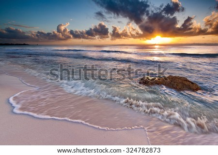 Caribbean Sunrise near Playa del Carmen, Riviera Maya, Mexico. The long exposure creates an artistic motion effect. - stock photo