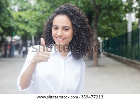 Caribbean woman with curly hair in a park showing thumb up - stock photo