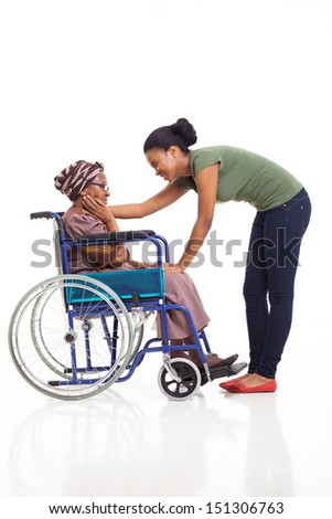 caring african woman comforting disabled senior mother on white background - stock photo