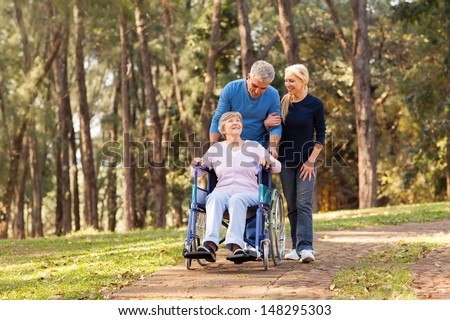caring couple taking their disable senior mother for a walk at the park - stock photo