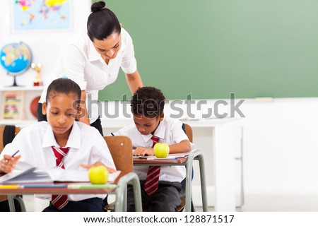 caring elementary school teacher and students in classroom - stock photo
