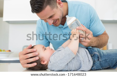 Caring father feeding milk to baby boy at kitchen counter - stock photo