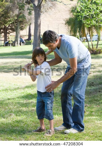 Caring father teaching baseball to his son in the park - stock photo