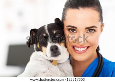 caring female vet holding a dog closeup portrait - stock photo