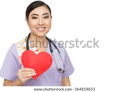Caring for you. An attractive Asian female doctor holding red paper heart smiling warmly to the camera isolated on white - stock photo