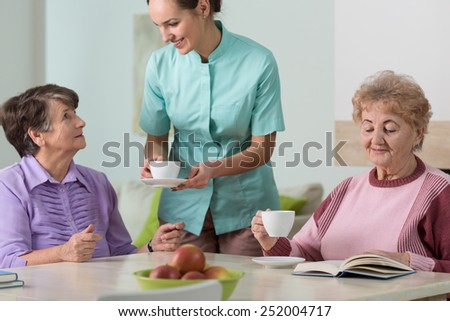 Caring nurse and residents of residential home - stock photo