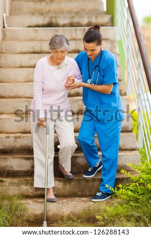 caring nurse helping senior patient walking down stairs - stock photo