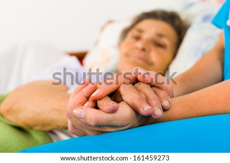 Caring nurse holding kind elderly lady's hands in bed. - stock photo