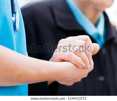 Caring nurse or doctor holding elderly lady's hand with care. - stock photo