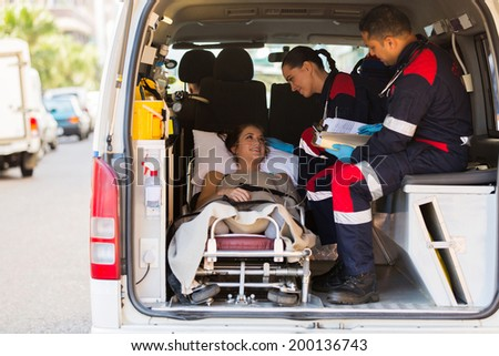 caring paramedic talking to patient in ambulance - stock photo