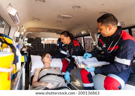 caring paramedics talking to patient on ambulance on the way to hospital - stock photo