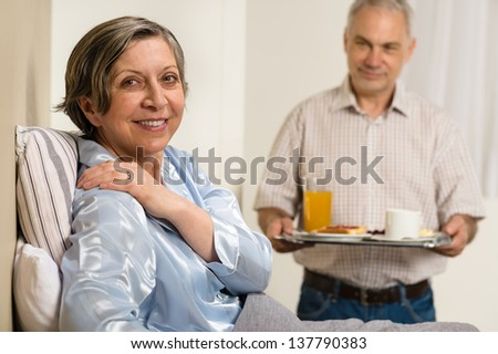Caring senior man bringing breakfast to her sick wife - stock photo