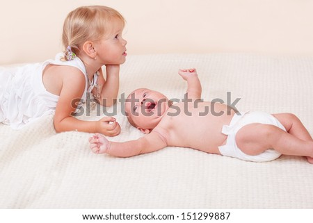 Caring sister and her infant brother lying on bed - stock photo