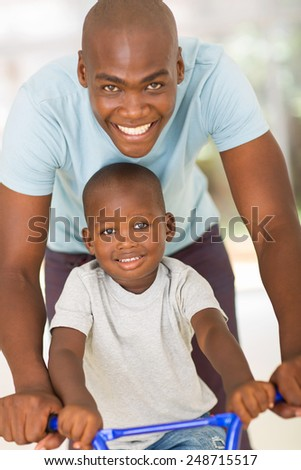 caring young african father pushing son on a bike - stock photo