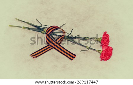 Carnation flowers and George Ribbon - a symbol of the Victory in the Great Patriotic War - stock photo