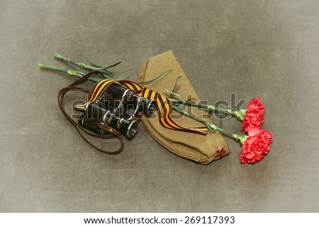 Carnation flowers, George Ribbon and military binoculars. Retro photo to Victory Day on May 9 - stock photo