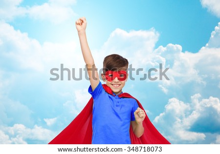 carnival, childhood, power, gesture and people concept - happy boy in red superhero cape and mask showing fists over blue sky and clouds background - stock photo