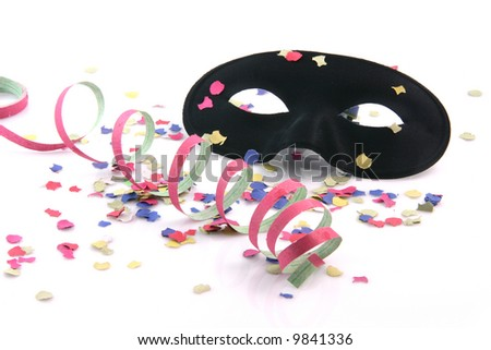 carnival concepts paper confetti streamers and black mask isolated on white background - stock photo