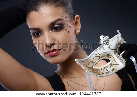 Carnival luxury, portrait of attractive woman in elegant party makeup holding decorated mask. - stock photo