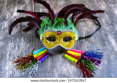 Carnival mask and blower on wood - stock photo