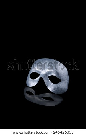 Carnival mask grey floating on a black background with reflection effect - stock photo