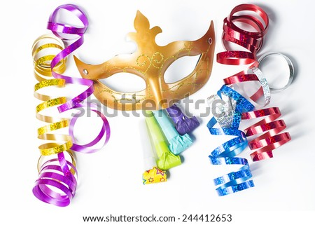 Carnival mask with colorful streamers and party horns on white background - stock photo