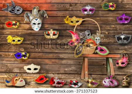 Carnival masks hanging on  wall boards lie on floor and  bench in a wicker basket set - stock photo