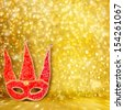 Carnival red mask on  gold abstract background with bokeh effect - stock photo