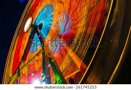 Carnival ride showing a spinning ferris wheel in action- long exposure shot. - stock photo