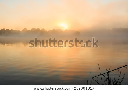 Carp fishing on a misty lake at sunrise in the center of France. - stock photo