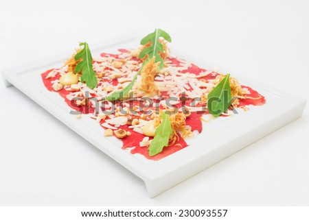 Carpaccio appetizer prepared at a restaurant, isolated on white, served on a white dish. Vertical format - stock photo