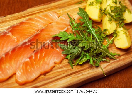 Carpaccio of salmon with boiled potato pieces, ruccola and fennel served on wooden board in restaurant. Close up - stock photo