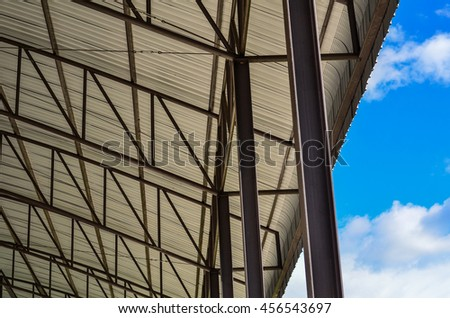 Carpark Detail of Metal roof construction and blue sky background. - stock photo