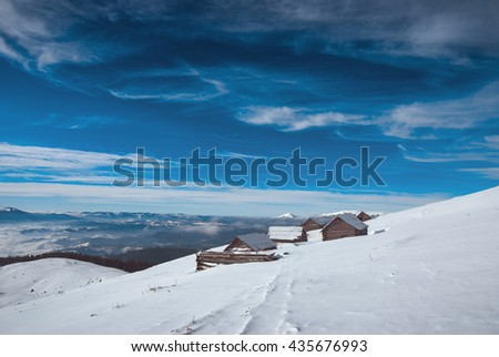 Carpathian mountain village with old rustic houses covered by snow. Frosty winter day. Ukraine, Europe - stock photo