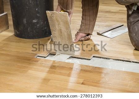 Carpenter Applying Parquet Glue - stock photo