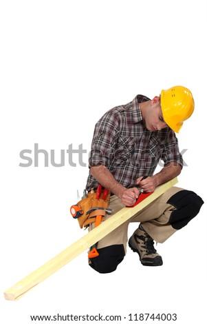 carpenter at work sharpening timber - stock photo