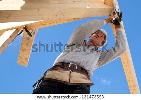 carpenter at work with wooden  roof construction - stock photo