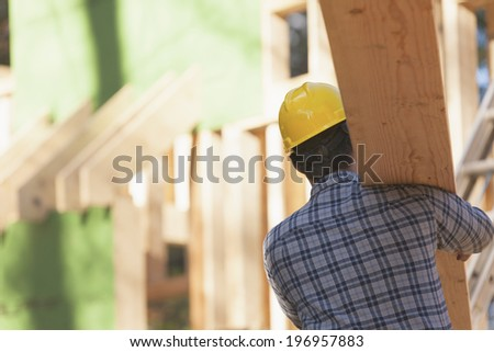 Carpenter carrying roof rafters on his shoulder - stock photo