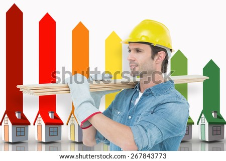 Carpenter carrying wooden planks over white background against seven 3d houses representing energy efficiency - stock photo