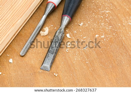 Carpenter chisel tool with shavings on wooden background - stock photo