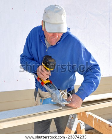 Carpenter cutting fibrous cement siding with power shears - stock photo