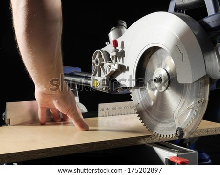 Carpenter cutting flaxboard using sliding compound mitre saw - stock photo