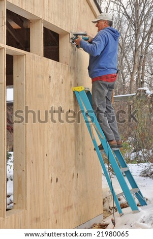Carpenter cutting openings in plywood sheathing for windows - stock photo