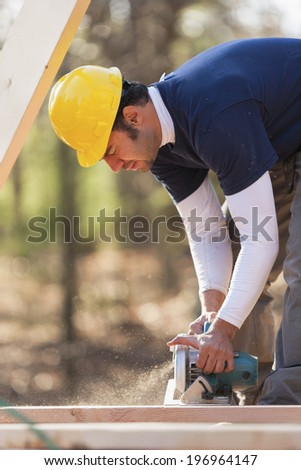 Carpenter cutting rafters and joists with circular saw - stock photo