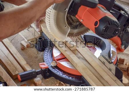 carpenter cutting timber - stock photo